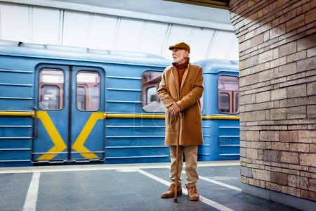 Photo for Aged man in autumn outfit standing with walking stick on metro platform near train - Royalty Free Image