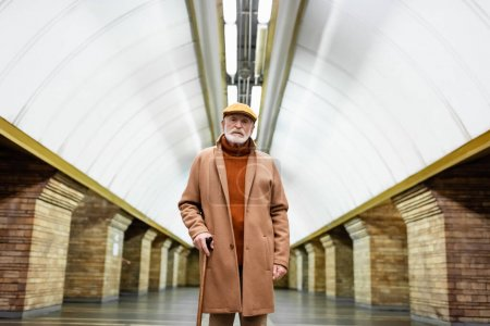 senior man in cap and autumn outfit looking at camera while standing with walking stick at a subway station