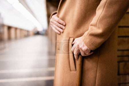 Photo for Partial view of senior man in coat standing with walking stick at metro station - Royalty Free Image