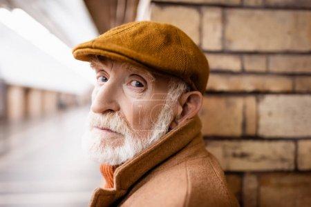 aged man in autumn cap looking at camera on metro platform