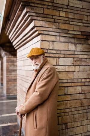 elderly man in autumn cap and coat standing with walking stick near brick column at metro station