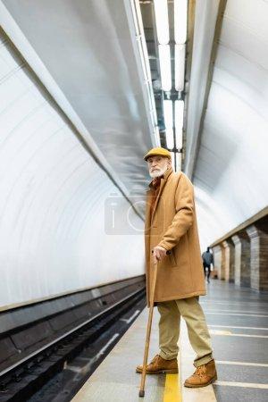 elderly man in autumn outfit standing on underground platform with walking stick
