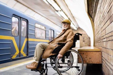 senior disabled man in wheelchair, wearing autumn outfit, near train on metro platform