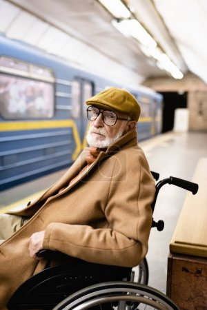 aged handicapped man in wheelchair, wearing autumn clothes, on metro platform near blurred train