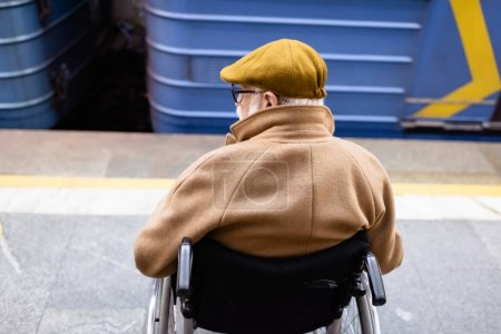 back view of senior disabled man in wheelchair, wearing autumn clothes, near blurred train on metro station