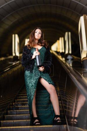 seductive woman in elegant black dress holding bottle of wine on underground escalator