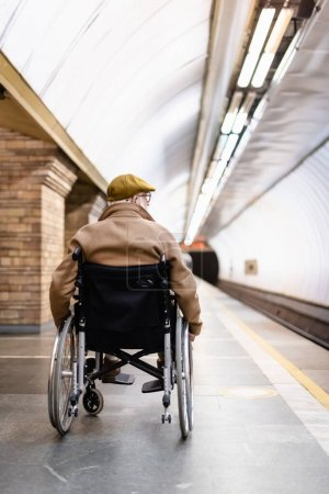 Photo for Back view of senior man in wheelchair, wearing coat and cap, on platform of metro station - Royalty Free Image