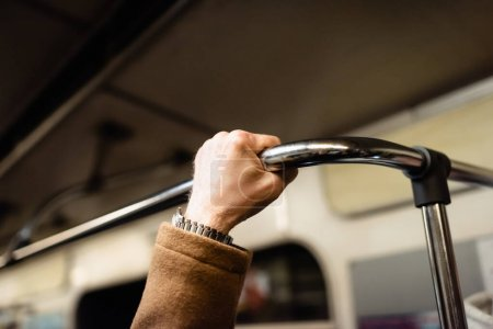 partial view of senior man holding handrail in wagon of subway train
