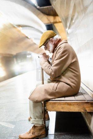 Foto de Side view of senior man sitting on bench with bowed head while train arriving on metro platform - Imagen libre de derechos