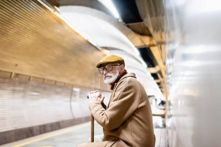 aged man in autumn outfit and eyeglasses sitting with walking stick on underground platform
