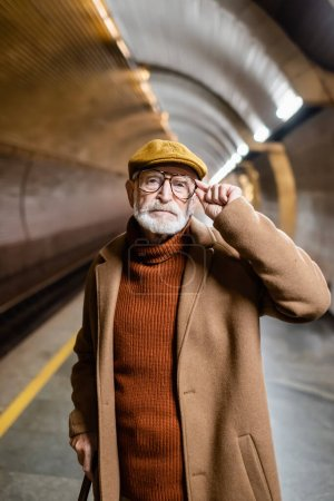 senior man in autumn cap and coat touching eyeglasses and looking at camera while standing on subway platform