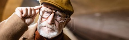 portrait of aged man in autumn cap touching eyeglasses while looking at camera, banner