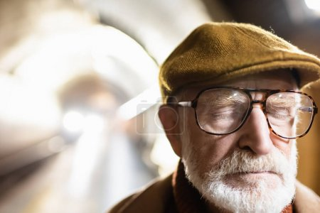 portrait of aged man in cap and eyeglasses standing with closed eyes on metro platform with light in metro tunnel on background