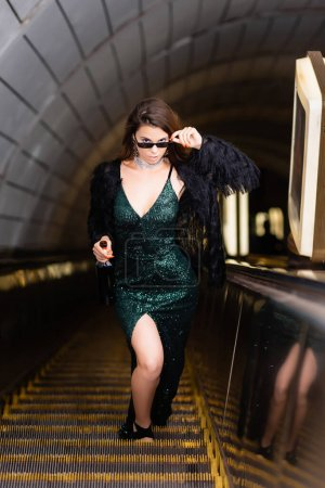 Photo pour Glamour femme en noir robe lurex toucher des lunettes de soleil tout en regardant la caméra sur l'escalator - image libre de droit