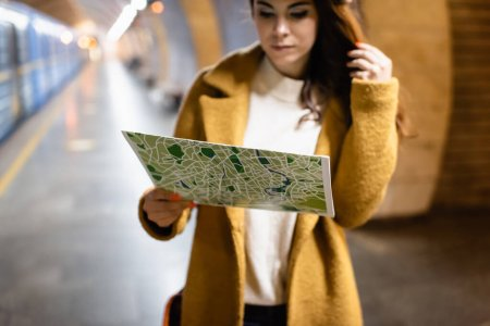 young woman in autumn coat studying city map on underground platform