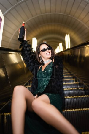 excited woman in elegant dress holding wine bottle in raised hand while sitting on escalator