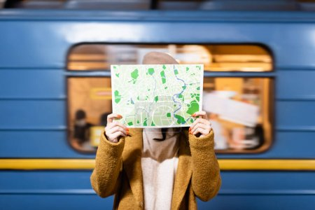 woman in autumn coat obscuring face with city map with blurred metro train on background