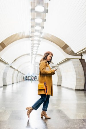 young woman in stylish autumn outfit chatting on smartphone on subway station