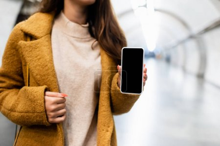 Photo for Partial view of woman in autumn clothes showing smartphone with blank screen at metro station - Royalty Free Image