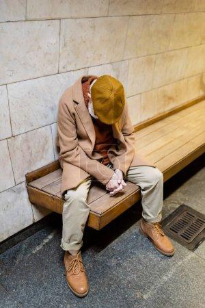 Photo pour Homme âgé en manteau d'automne et chapeau dormir sur banc plate-forme souterraine - image libre de droit