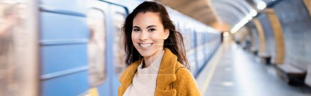 happy young woman looking at camera on underground platform with blurred train, banner