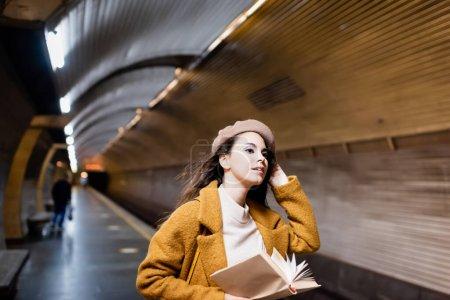 Photo pour Femme élégante en automne vêtements tenant livre et regardant loin sur la plate-forme de métro - image libre de droit