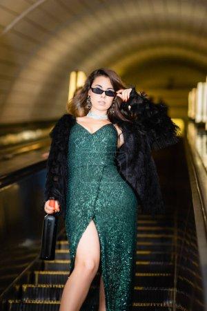 Photo pour Vue recadrée de glamour femme posant sur escalator avec bouteille de vin - image libre de droit