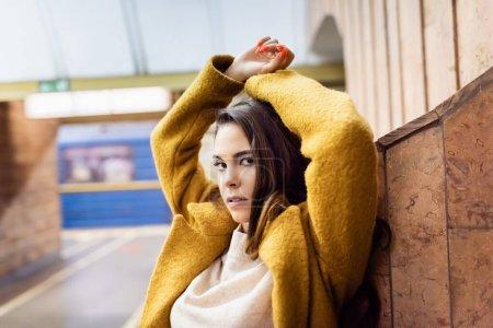 young stylish woman looking at camera while posing near wall at metro station
