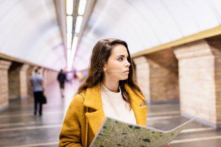 Photo pour Jeune femme en manteau d'automne regardant loin tout en tenant la carte de la ville à la station de métro - image libre de droit
