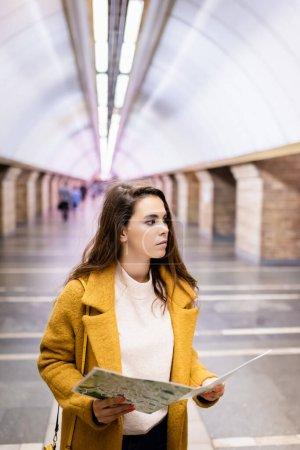 Photo pour Jeune femme en manteau d'automne élégant regardant loin tout en tenant la carte de la ville à la station de métro - image libre de droit