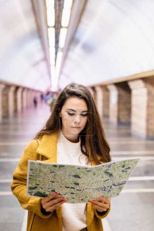 young woman in autumn clothes studying city map at underground station