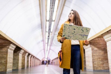 stylish woman in autumn outfit holding city map and looking away at underground station