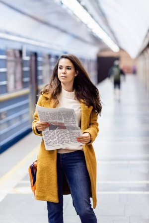 young woman in autumn outfit holding newspaper near blurred metro train on platform