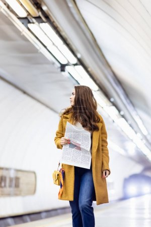 Photo for Young woman in coat holding newspaper while walking along underground platform - Royalty Free Image