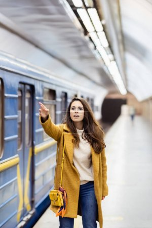young woman in autumn outfit gesturing with outstretched hand near blurred train on metro platform