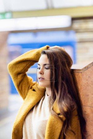 Photo pour Jeune femme en tenue d'automne touchant les cheveux tout en se tenant près du mur à la station souterraine - image libre de droit