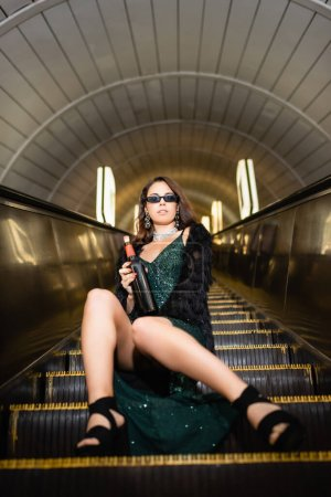 sensual woman in lurex dress and black faux fur jacket sitting on escalator with wine bottle on blurred foreground
