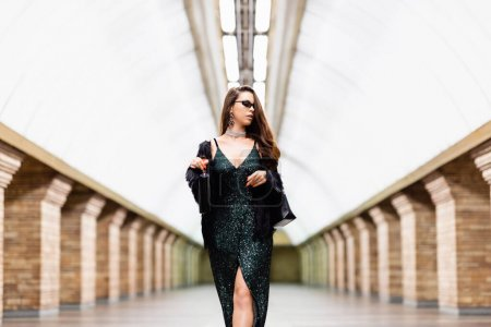 Photo for Seductive, stylish woman in black lurex dress standing with bottle of wine on subway station - Royalty Free Image