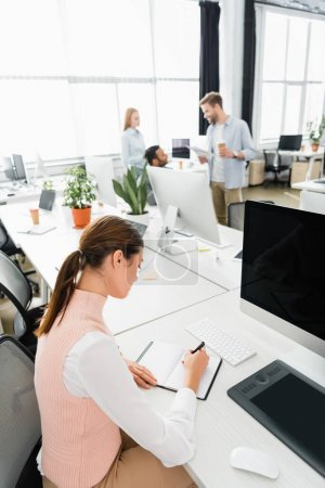 Businesswoman writing on notebook near computer and colleagues on blurred background in office