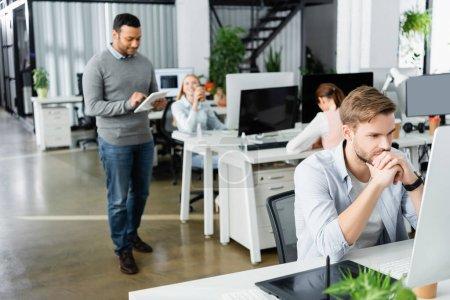 Photo pour Homme d'affaires utilisant un ordinateur près de tablette graphique et des collègues multiethniques sur fond flou dans le bureau - image libre de droit