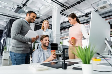 Smiling multicultural businesspeople with devices and coffee to go talking in office