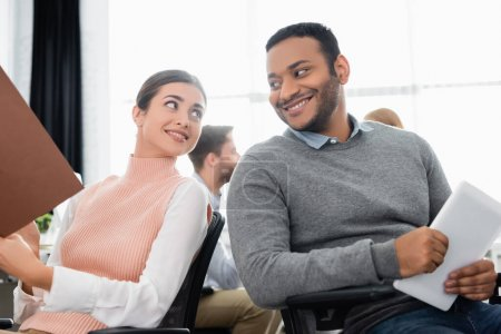 Smiling businesswoman with paper folder looking at indian colleague with digital tablet in office