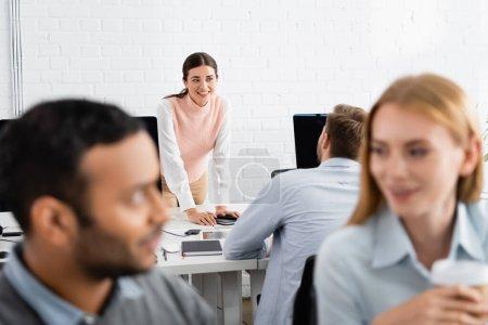 Lächelnde Geschäftsfrau blickt Kollegin in der Nähe von Geräten im Büro an