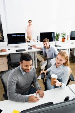 Cheerful multiethnic businesspeople looking at computer in office