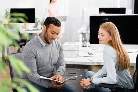 Hombre de negocios indio sosteniendo una carpeta de papel cerca de un colega sonriente y una computadora en la oficina