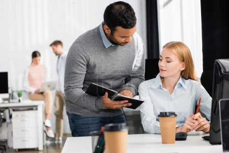 Photo for Indian businessman holding notebook near businesswoman and coffee to go on blurred foreground - Royalty Free Image