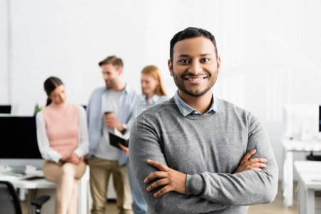 Photo for Smiling indian businessman with crossed arms standing near colleagues on blurred background in office - Royalty Free Image