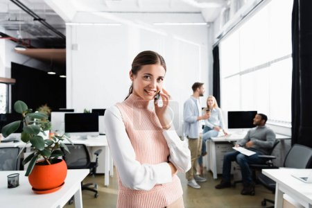 Positive businesswoman talking on smartphone while colleagues working on blurred background in office