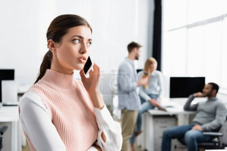 Young businesswoman talking on smartphone with colleagues on blurred background in office