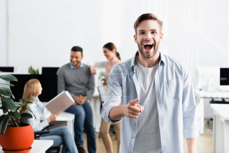 Excited businessman pointing with finger at camera near multiethnic colleagues on blurred background
